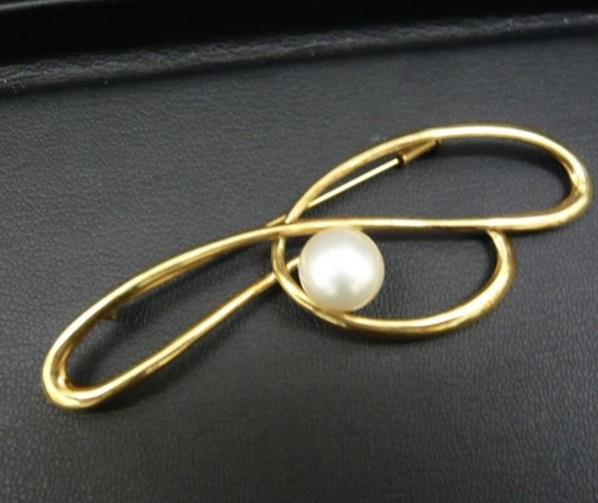 真珠のついた金のブローチ
